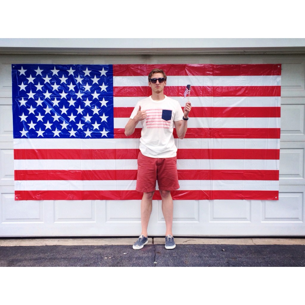 my husband posing in front of the 10ft  flag we bought for the garage